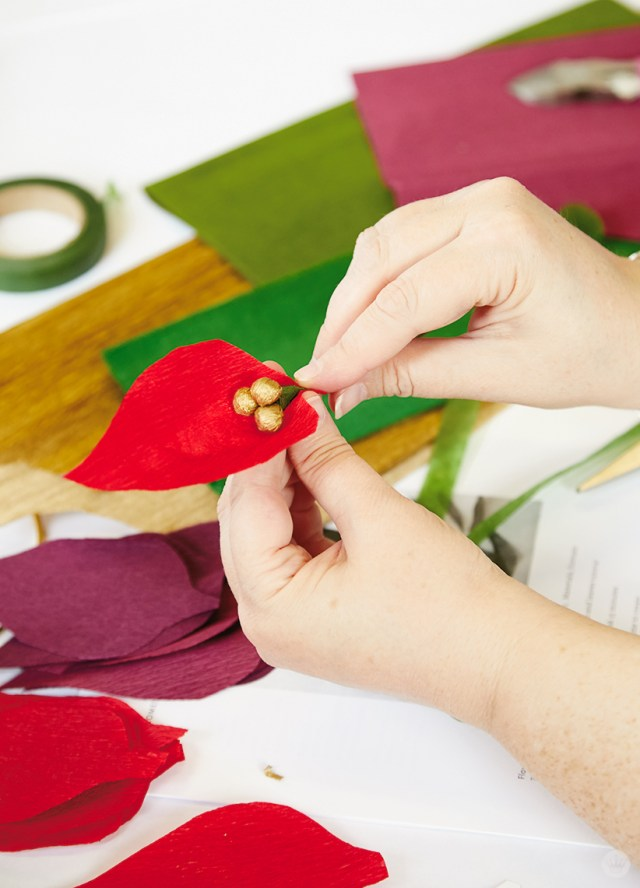 Wrapping petals on a crepe paper poinsettia