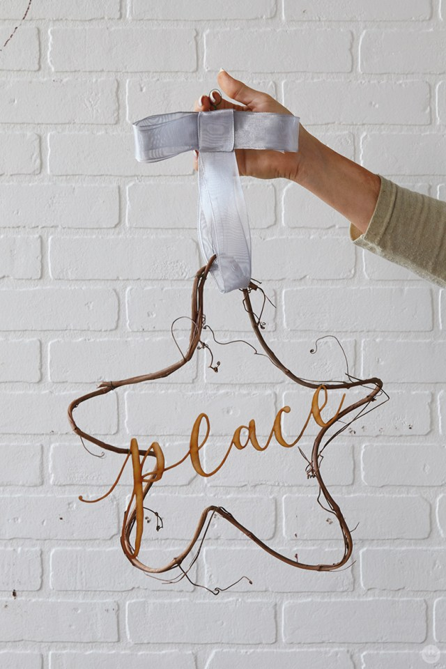 "Modern Christmas wreath ideas: Star-shaped vine wreath with laser-cut ""peace"""