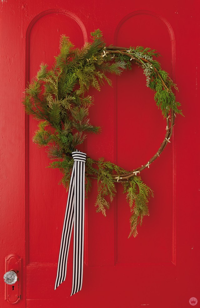Modern Christmas wreath ideas: Asymmetrical wreath with black and white ribbon
