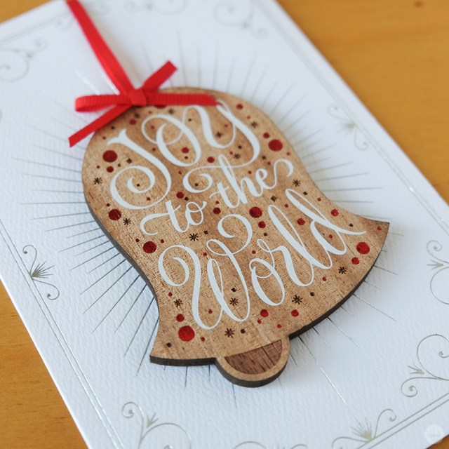 Wooden bell ornament on foil-accented card.