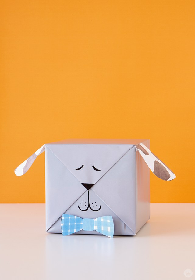 Kids gift wrap idea: gray box with paper ears and bowtie attachments to turn it into a dog.