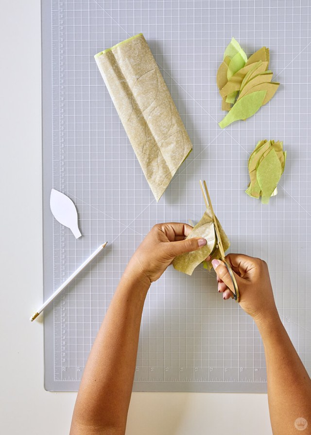 Cutting out the leaf shapes from the tissue paper for the DIY paper vine garland | thinkmakeshareblog.com