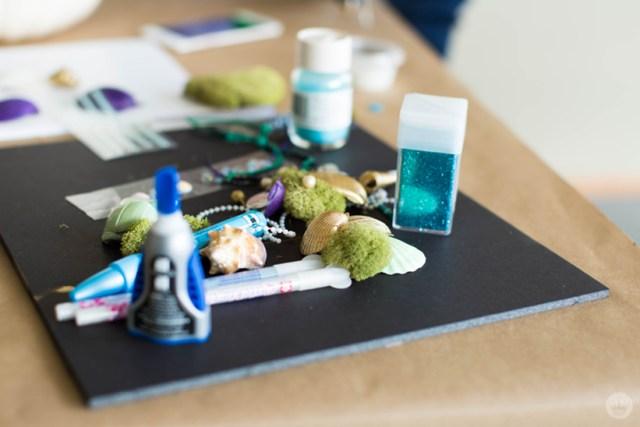 Supplies for movie-inspired pumpkin designs: glue, shells, moss, paint pens, and glitter.