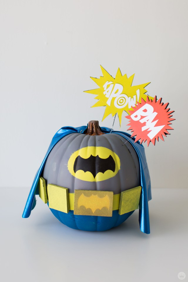 """Pumpkin painted in gray, blue, and yellow—including a blue fabric cape—to resemble Batman's costume from the 1960s television show based on the DC comic book character. Starbursts on top of the pumpkin say """"KAPOW!"""" and """"BAM."""""""