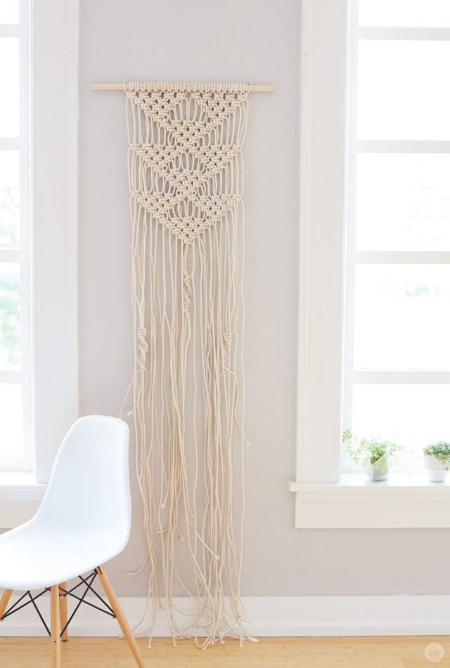 Large macramé wall hanging in white displayed on gray wall.