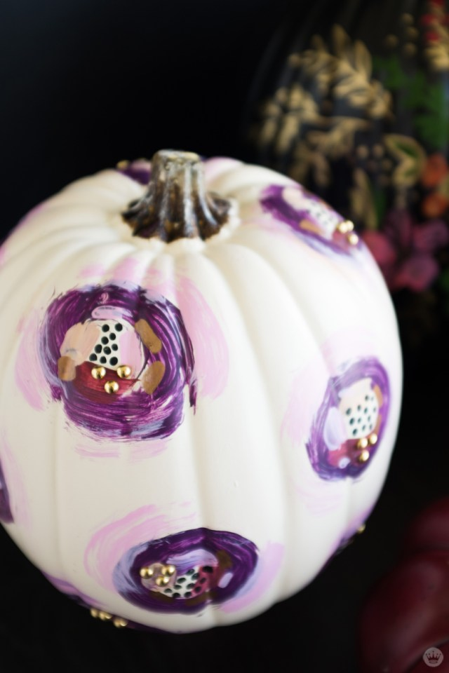 Elegant pumpkin designs: White pumpkin decorated with abstract purple pattern: circles with gold metallic studs