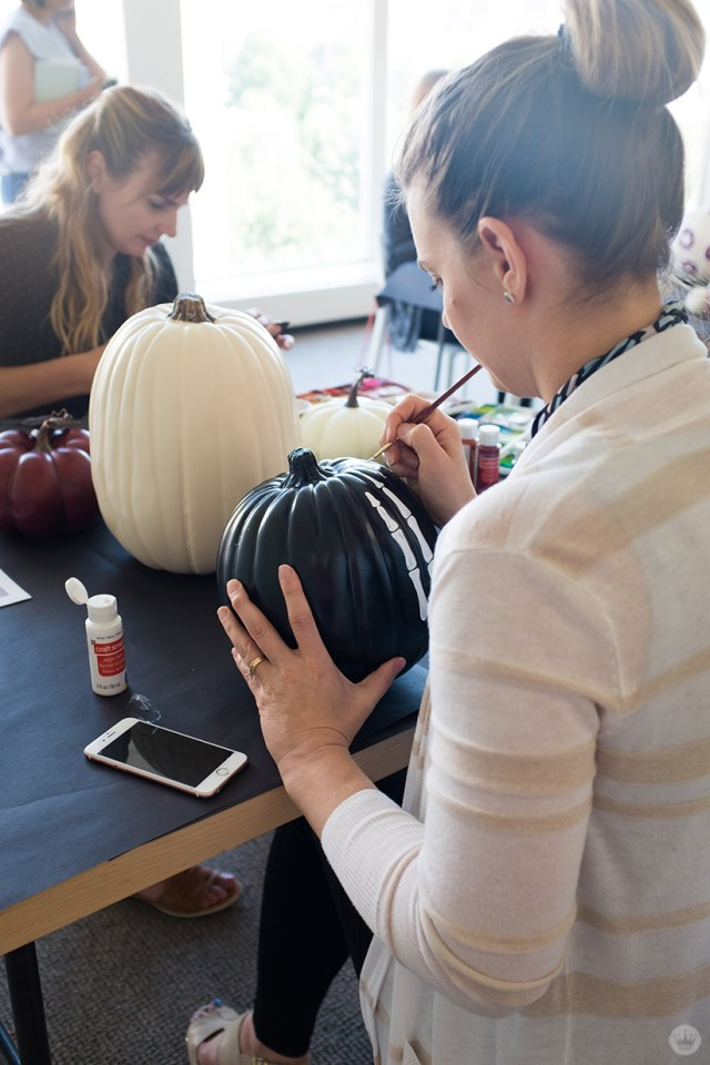 Artist painting a skeleton hand on a black pumpkin