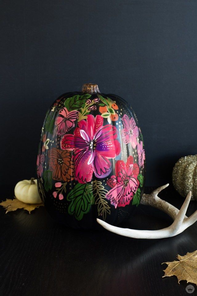 Elegant pumpkin designs: Black pumpkin painted with vivid flowers with gold accents