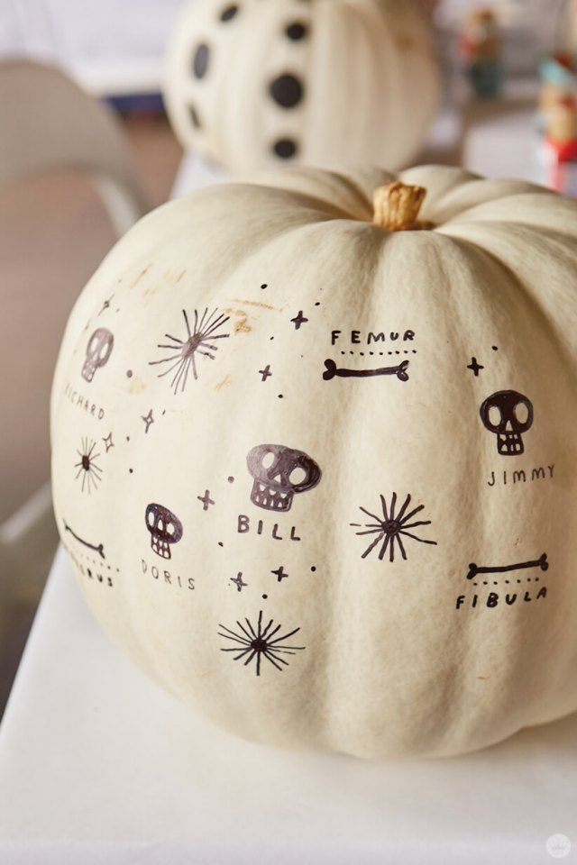 Tiny doodles of skulls and bones on a white pumpkin