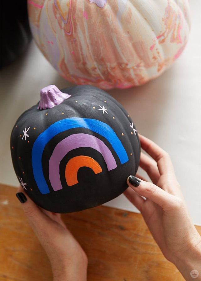 A white pumpkin with a marbled design and a black pumpkin with a blue, lavender, and orange mini-rainbow
