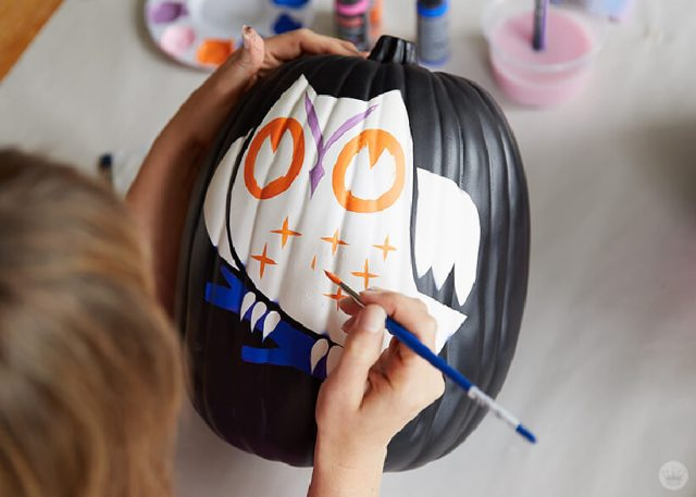 Painting an owl design on a black craft pumpkin