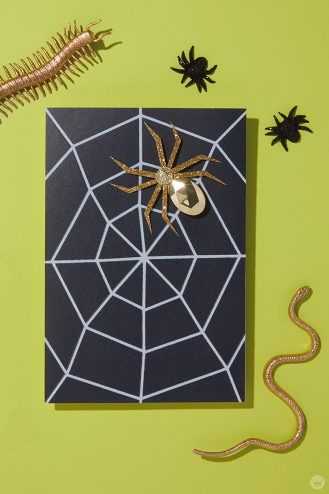 The Signature card behind our signature Halloween cocktail, the Crawls-mopolitan: Golden spider on black card with white web (also shown, gold centipede and worm, small black spiders)