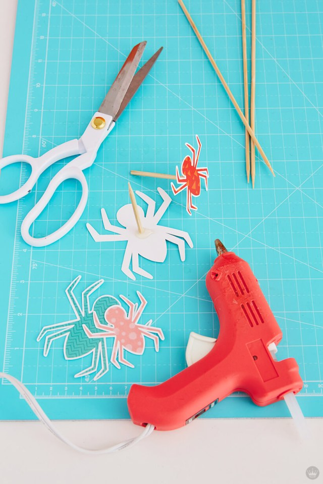 Assembling spider cake toppers with scissors, glue gun and wooden skewers