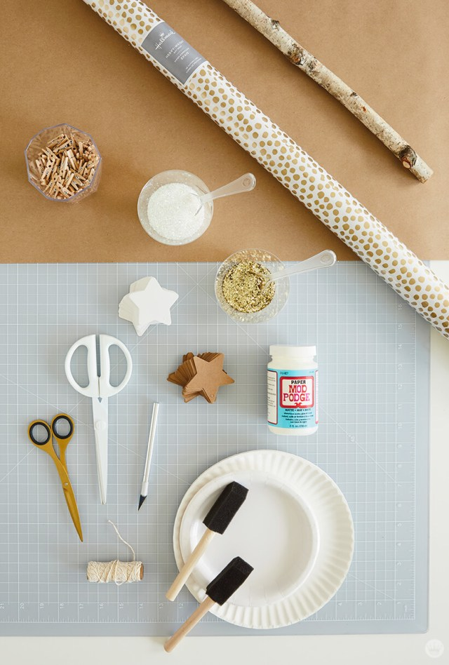 Supplies for the DIY Star Wall Hanging: branch, wrapping paper, mini clothes pins, craft glue, glitter, paper stars, scissors, craft knife, twine, paper plates, foam brushes | thinkmakeshareblog.com