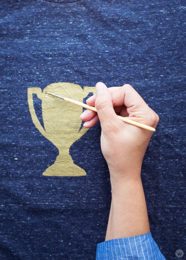 Touching up the screen print trophy t-shirt with a paint brush