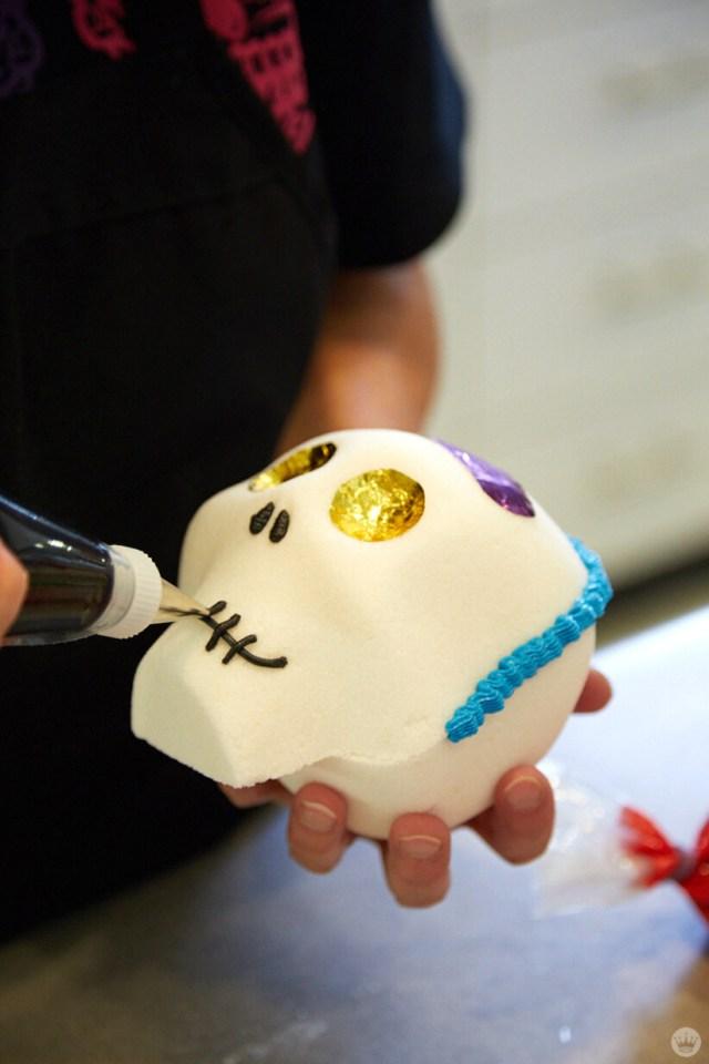 A sugar skull being decorated by a Hallmark Artist