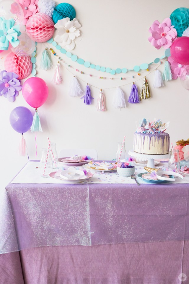 Unicorn Party ideas: Table covered with layered, shimmery cloths, set with mis-matched china, balloons and garlands as backdrop