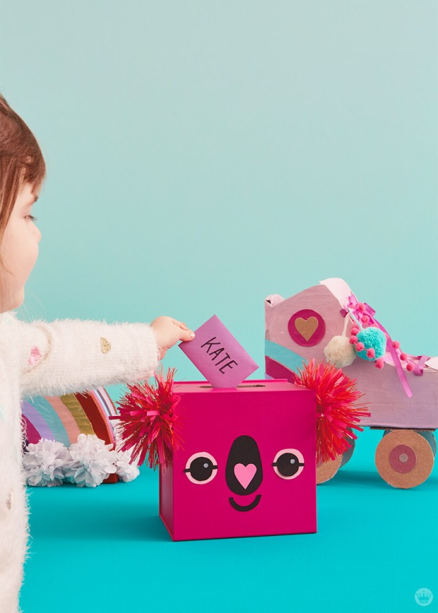 Girl placing valentine card in Koala mailbox—roller skate and rainbow mailboxes in background | thinkmakeshareblog.com