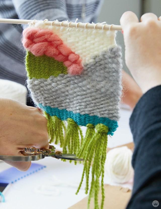 Weaving workshop: hallmark artist cuts tassels on small piece of fiber art