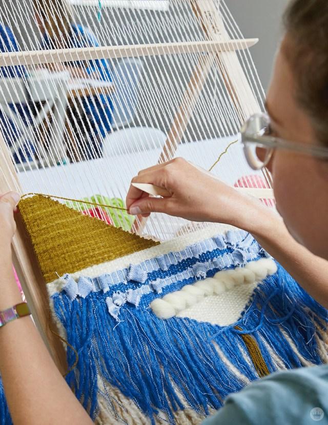 Weaving workshop: hallmark artist weaves fiber art piece on large loom with multiple materials