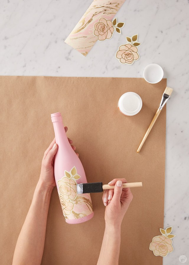 Upcycled wine bottle: Gluing wrapping paper designs to wine bottles   thinkmakeshareblog.com