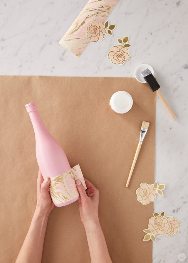 Upcycled wine bottles: Gluing wrapping paper designs to wine bottles | thinkmakeshareblog.com