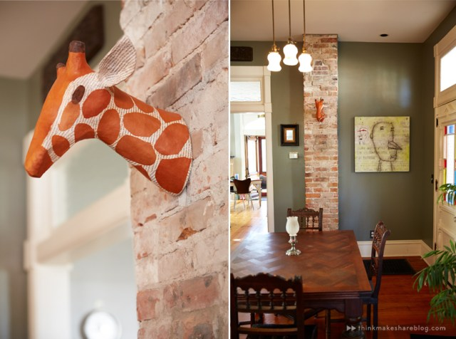 Tips for displaying art: A paper mache giraffe bust hangs on a brick column in a dining room