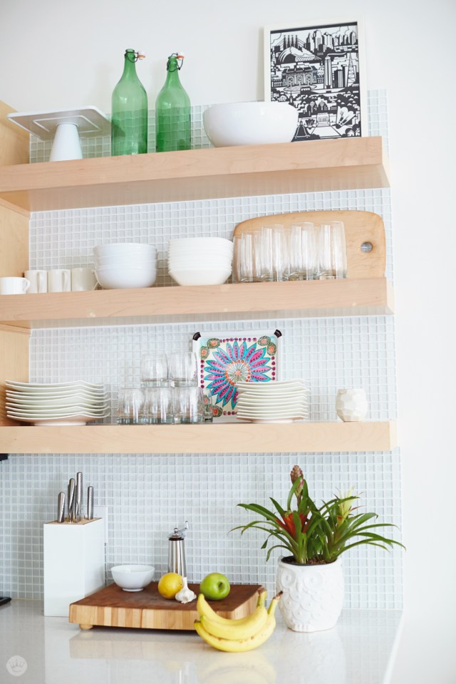 Tips for displaying art: Two small pieces of art (framed and tile) displayed on open kitchen shelving over a counter