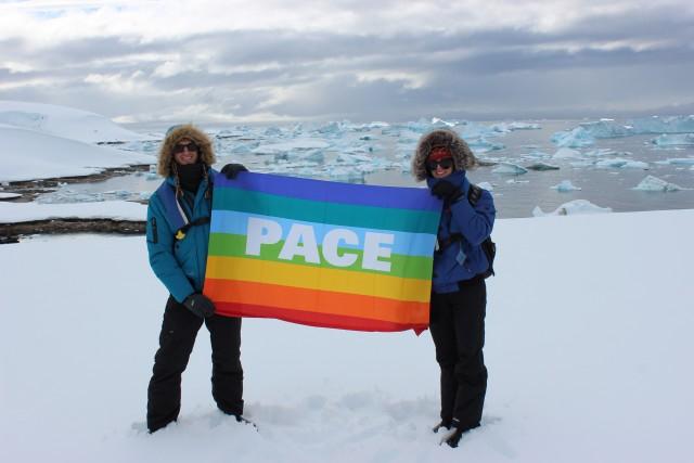 """Chelsea and Ryan holding an Italian """"Peace"""" flag on Antarctica"""