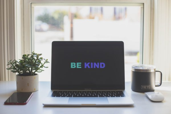 Laptop showing be kind on the screen