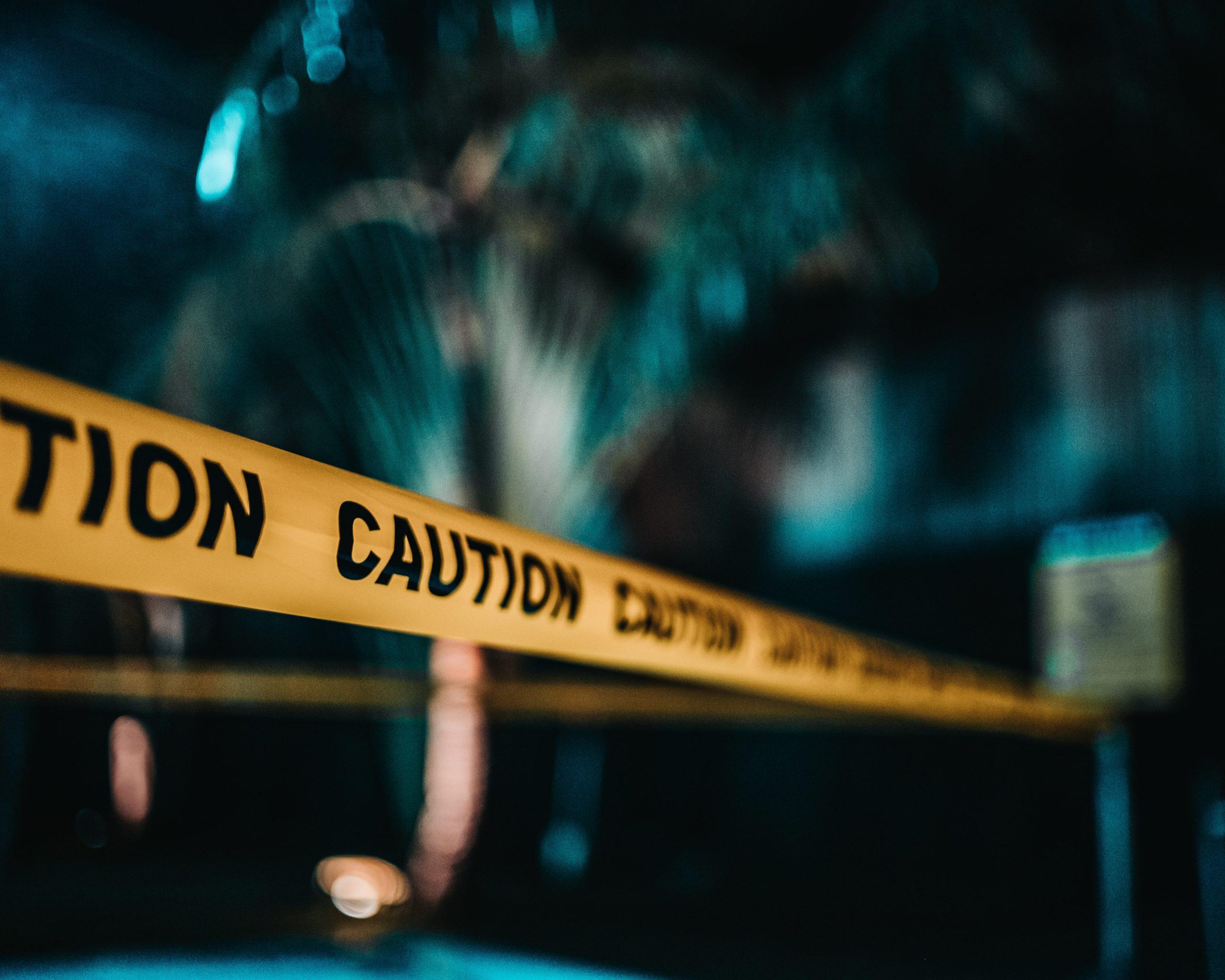 Yellow caution tape around blurred trees at night