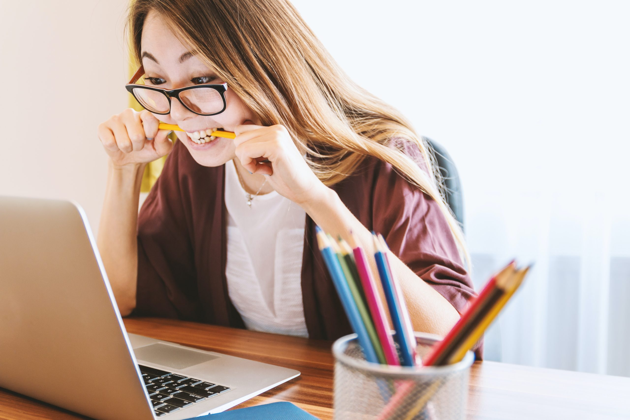Woman biting a pencil while looking at a laptop