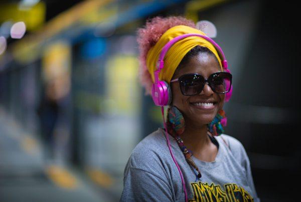 Smiling women wearing headphones on a train platform