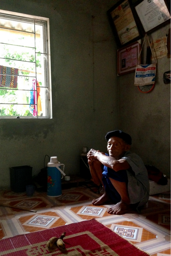 Image of an older Vietnamese man in his home crouching in the shadows in Xom Pung village Vietnam.