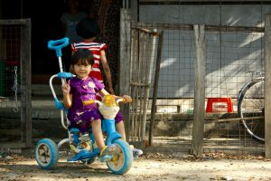 An image of a sassy young girl in Dala riding her bicycle and posing for the camera.