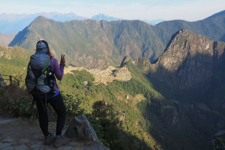 Image of me wearing my backpack looking down at Machu Picchu from the Sun Gate on Day 4 of the Inca Trail hike.