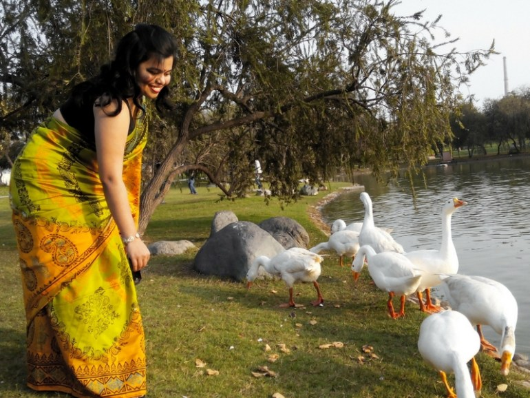 Image of blogger Orange Wayfarer feeding geese at Lodhi Garden in New Delhi India.