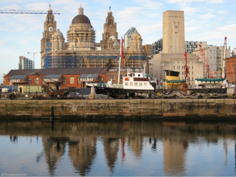 Image of the Liverpool skyline reflecting in the water at Albert Dock in Liverpool England.