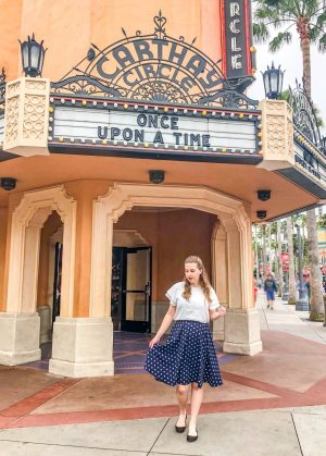 "Girl with white shirt and blue skirt stands out front of Carthay Circle. A large letter board on the building reads ""Once Upon a Time""."