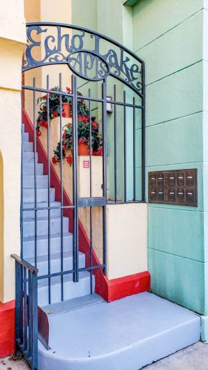 A gate to echo lake apartments. The wall is teal and the stairs are purple with red lining. There are mailbox slots along the teal wall, just outside the gate. This is located in the Echo Lake section of Disney's Hollywood Studios.