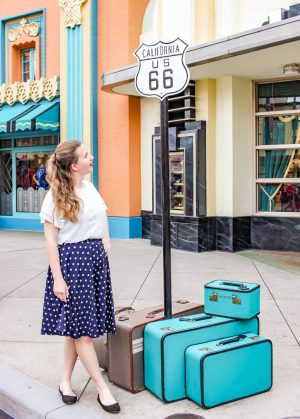 Girl with white shirt and blue skirt stands next to several suitcases a sign that says Route 66 at Disney Hollywood Studios.