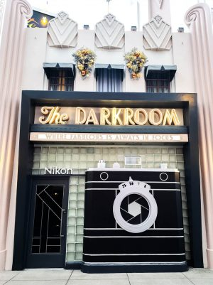 "The Darkroom at Disney Hollywood Studios looks like an vintage camera, with a door to it's left and glass tiles covering the outside walls. Above the tiles is a neon sign that reads ""The Darkroom""."