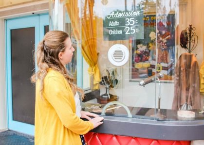 Girl with medium-length brown hair and a yellow jacket stands at the window of a fake ticket booth, looking at the sign of admission prices (Adults 35 cents, Children 25 cents).