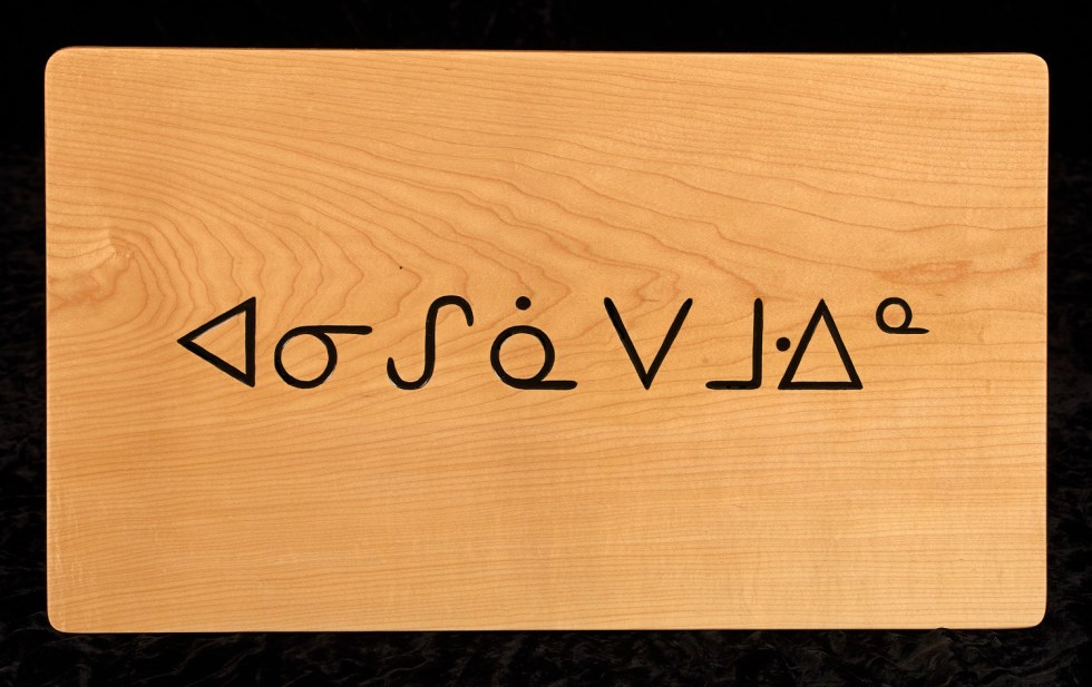 A carving by Tim Brookes in Ojibwe, a Canadian Aboriginal syllabic language