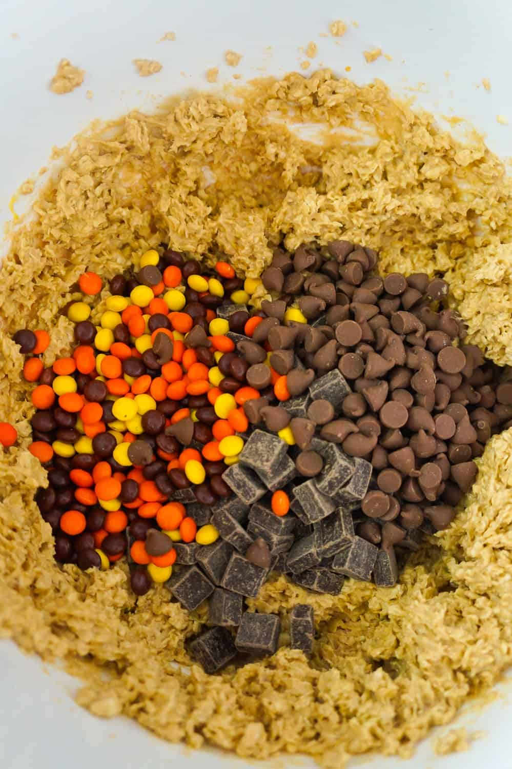 mini Reese's Pieces, milk chocolate chips and chocolate chunks on top of peanut butter oatmeal cookie dough