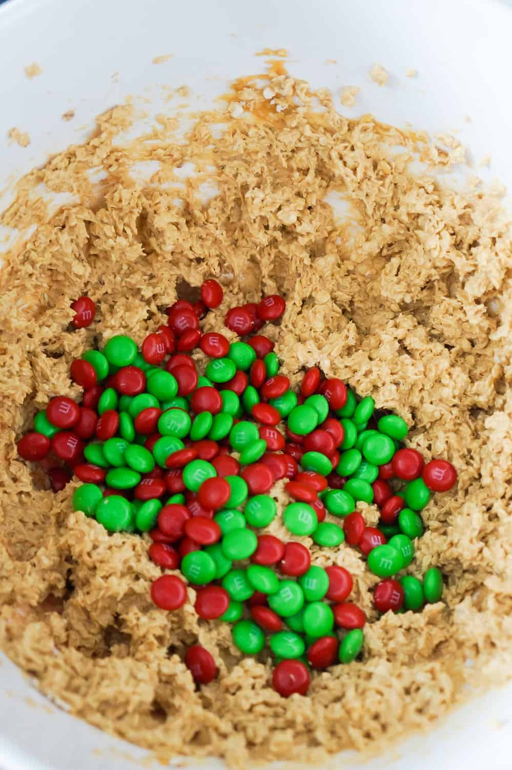 red and green M&Ms on top of peanut butter oatmeal cookie dough in a mixing bowl