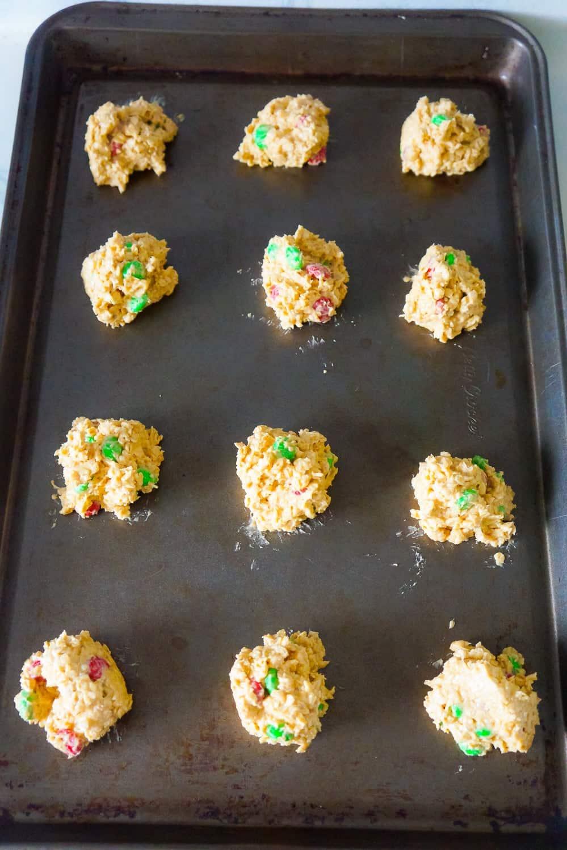 balls of Christmas monster cookie dough on a baking shet