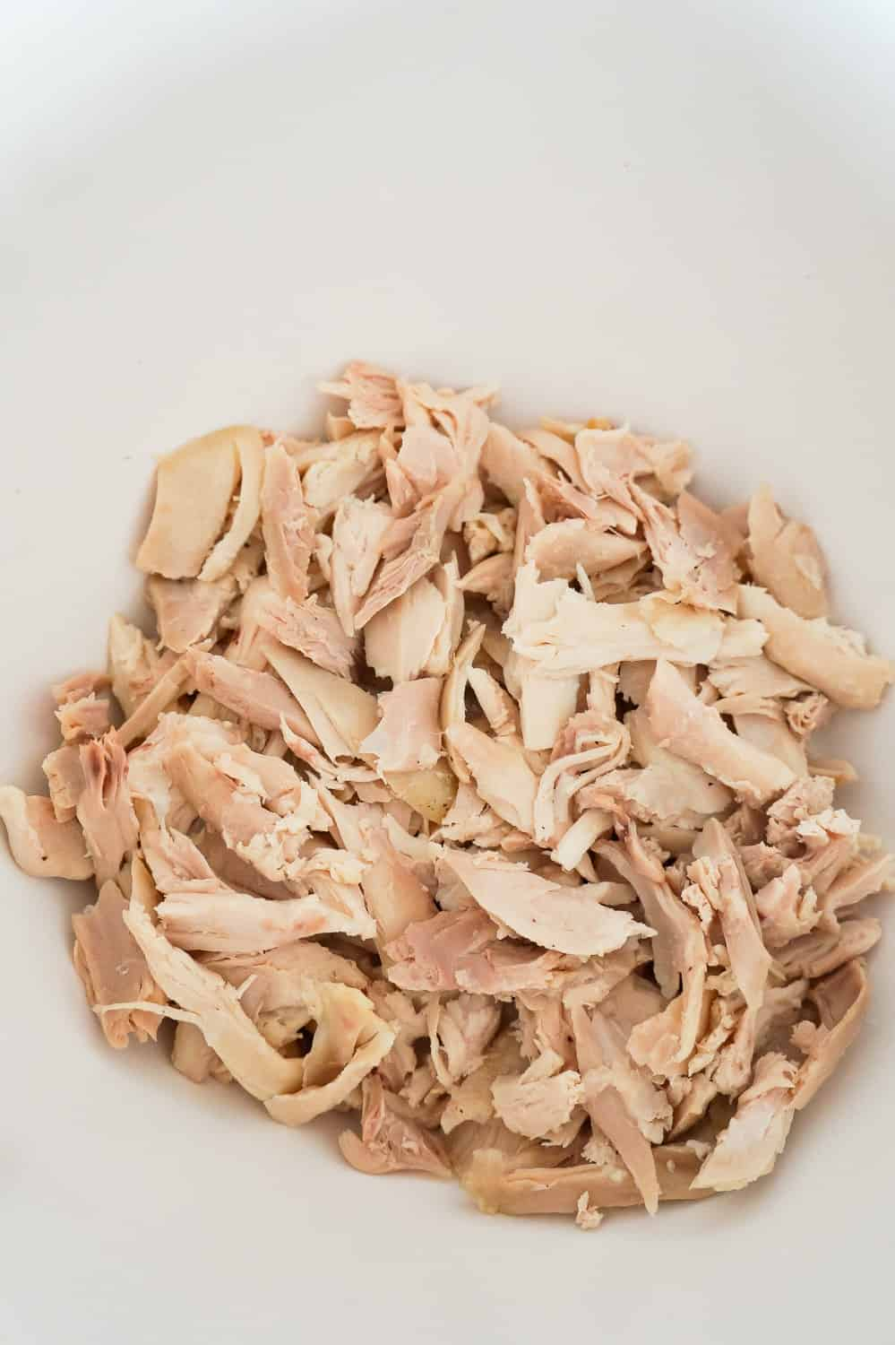 shredded rotisserie chicken in a mixing bowl