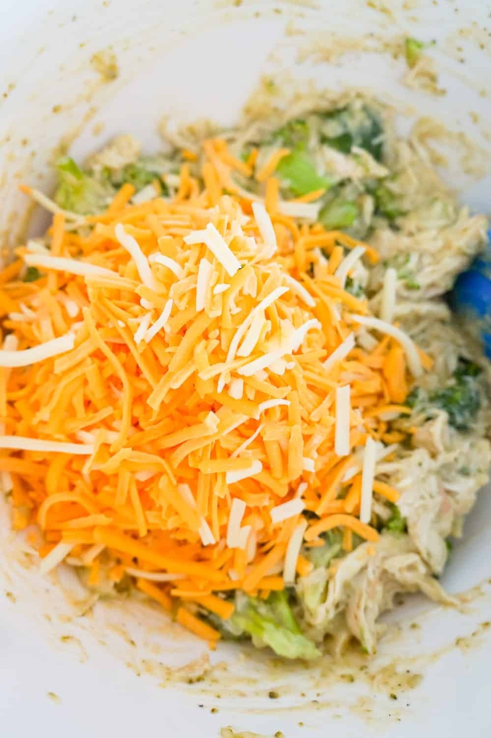 shredded cheddar cheese on top of chicken and broccoli mixture in a mixing bowl