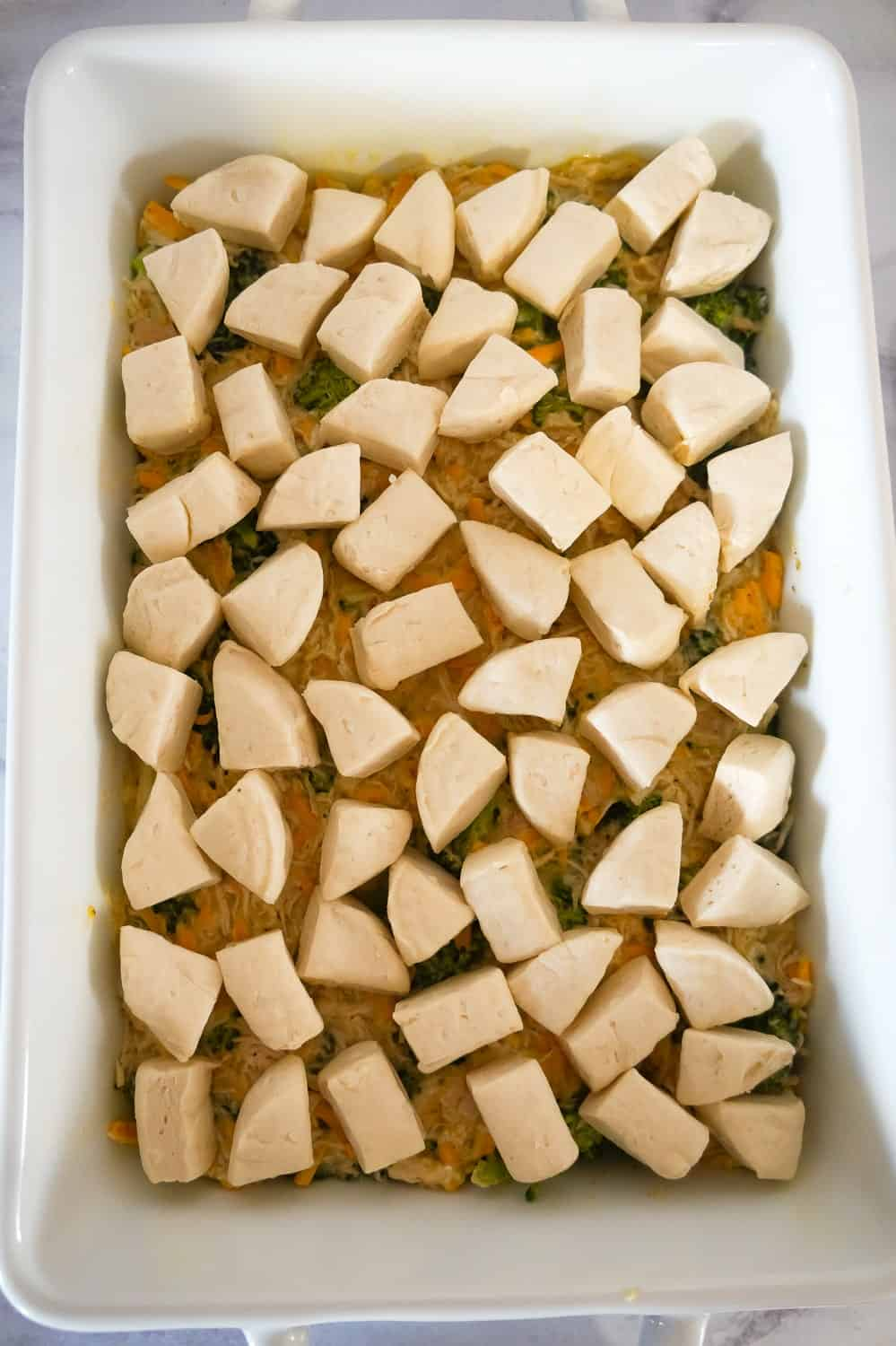 biscuit dough pieces on top of chicken and broccoli mixture in a baking dish